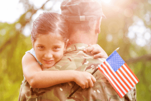 veteran father holding young daughter